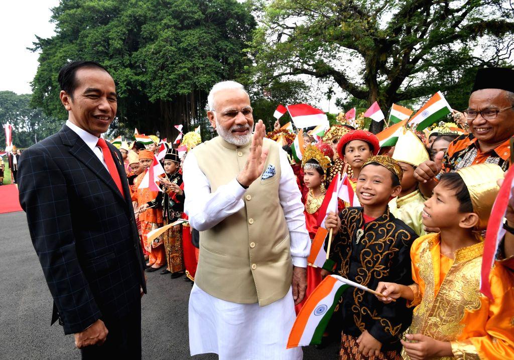 Indonesian President Joko Widodo welcomes Prime Minister Narendra Modi on his arrival at Istana Merdeka, in Jakarta of Indonesia on May 30, 2018. - Narendra Modi