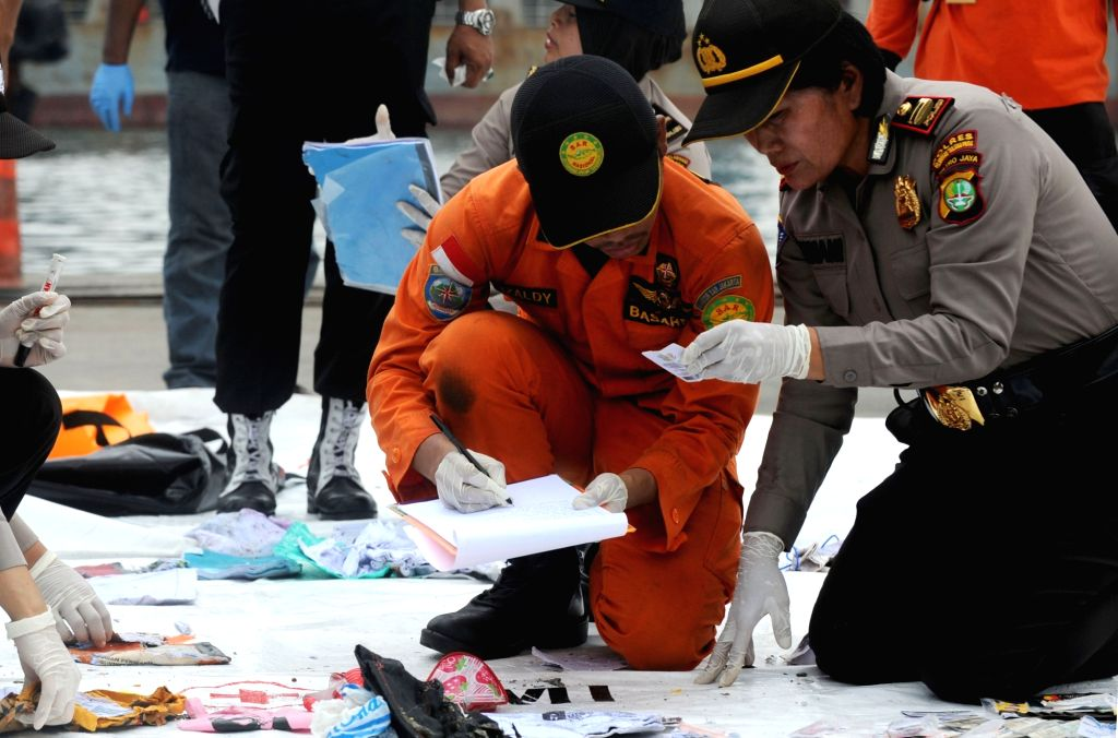 :Indonesian Search and Rescue (SAR) member and police officers check belongings of Lion Air Flight JT 610 victims at Jakarta International Container Terminal ...