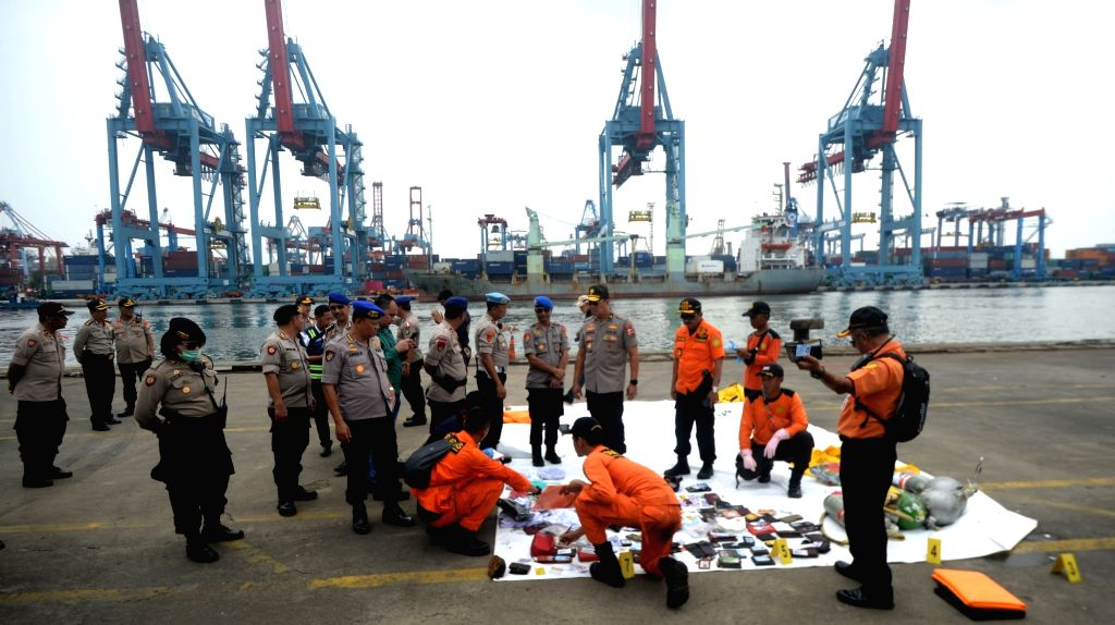 :Indonesian Search and Rescue (SAR) members and police officers check belongings of Lion Air Flight JT 610 victims at Jakarta International Container Terminal ...