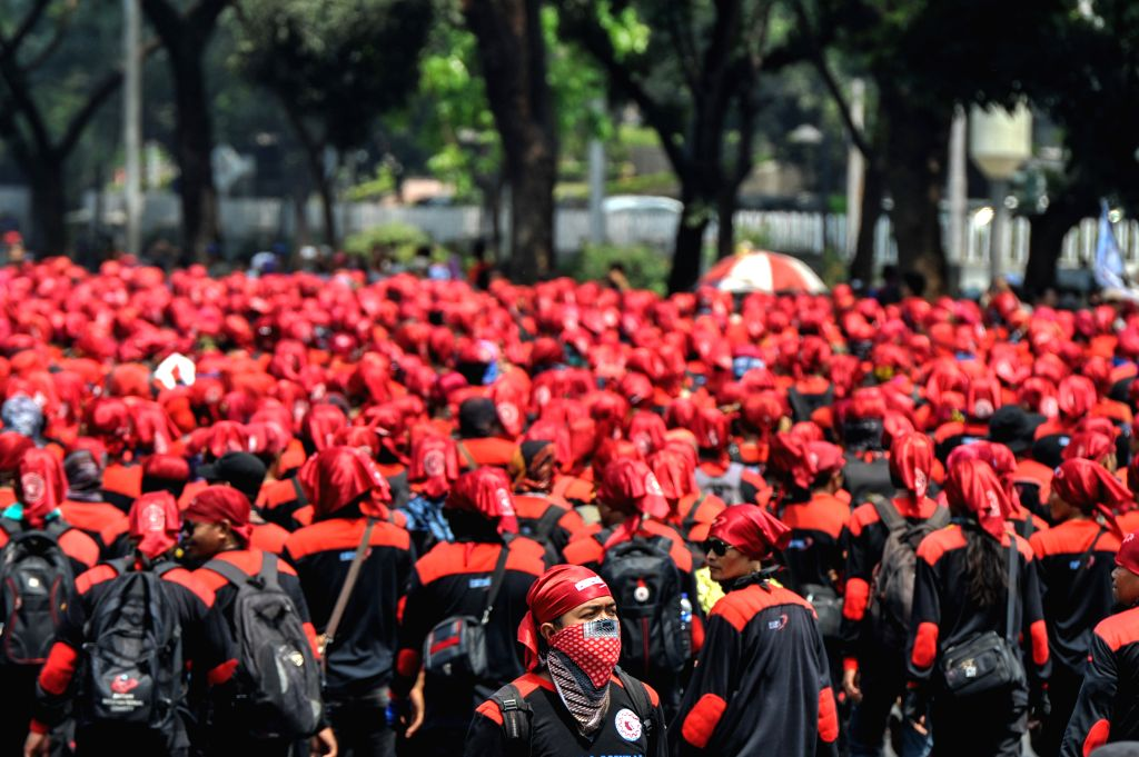 Indonesian workers gather at Patung Kuda (Horse Statue) fountain to walk to the presidential palace during the rally to refuse government's regulation on wage in ...