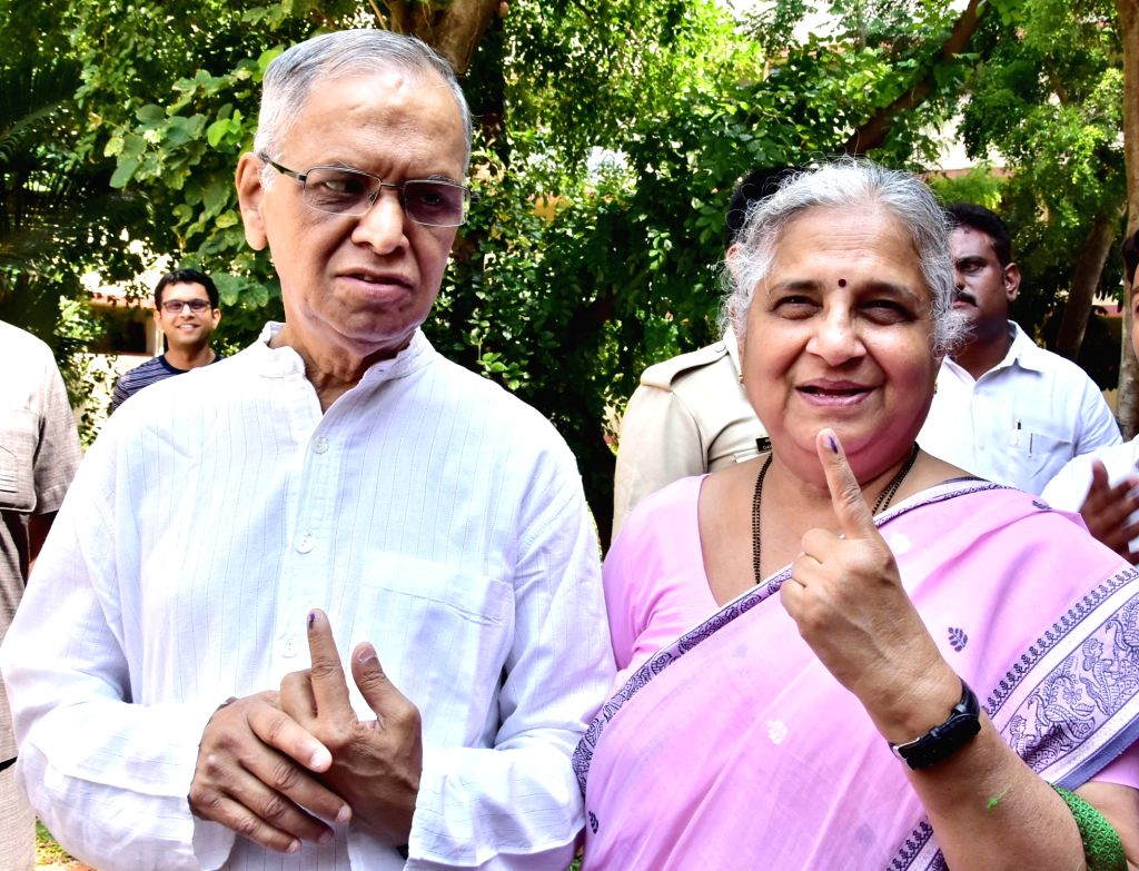 Infosys Founder N.R. Narayana Murthy looks on as his wife Sudha Murthy shows her inked finger, after casting their votes for the second phase of 2019 Lok Sabha elections in Bengaluru, on ...
