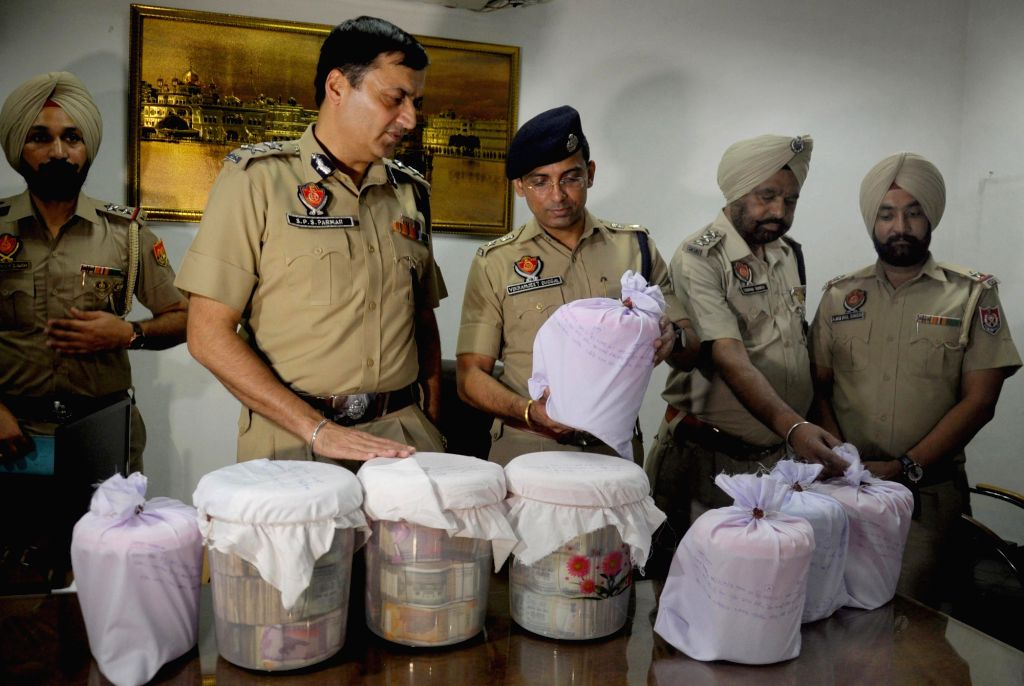 Inspector General (Border Range) SPS Parmar presents before press heroin seized from a smuggler in Amritsar on Sep 13, 2019.