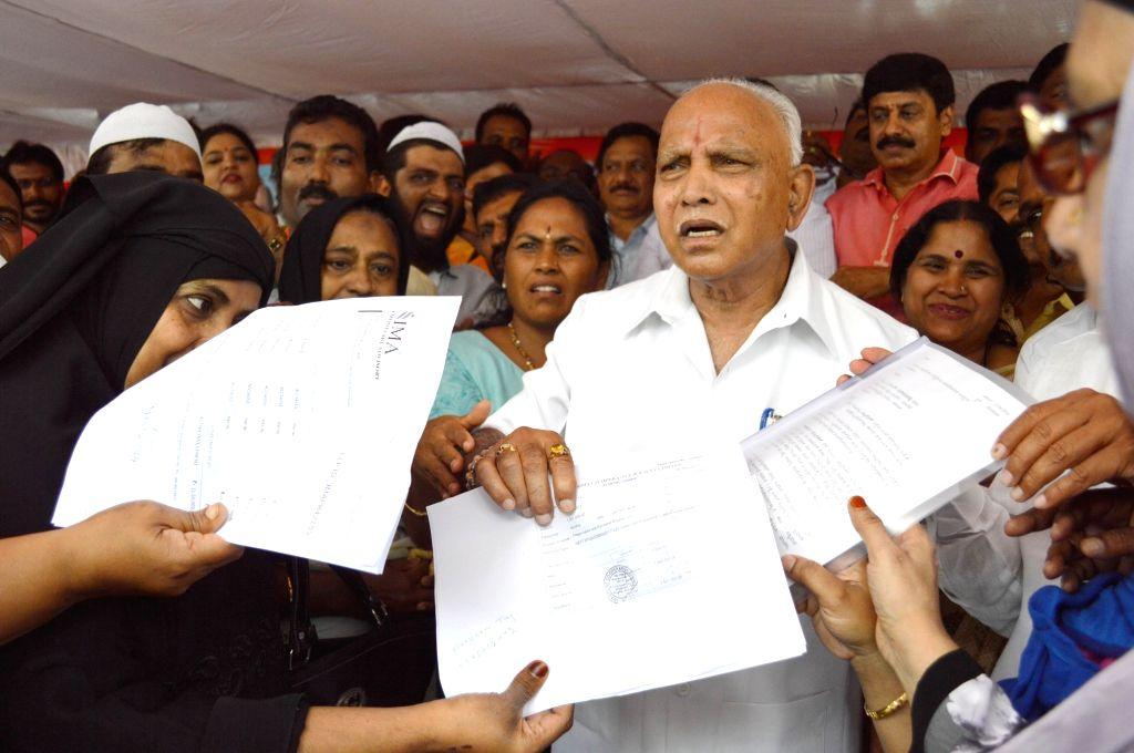 Investors of IMA Group of Companies, that is being probed for the alleged Ponzi scam, submit memorandum to Karnataka BJP President B.S. Yeddyurappa, in Bengaluru on June 15, 2019.