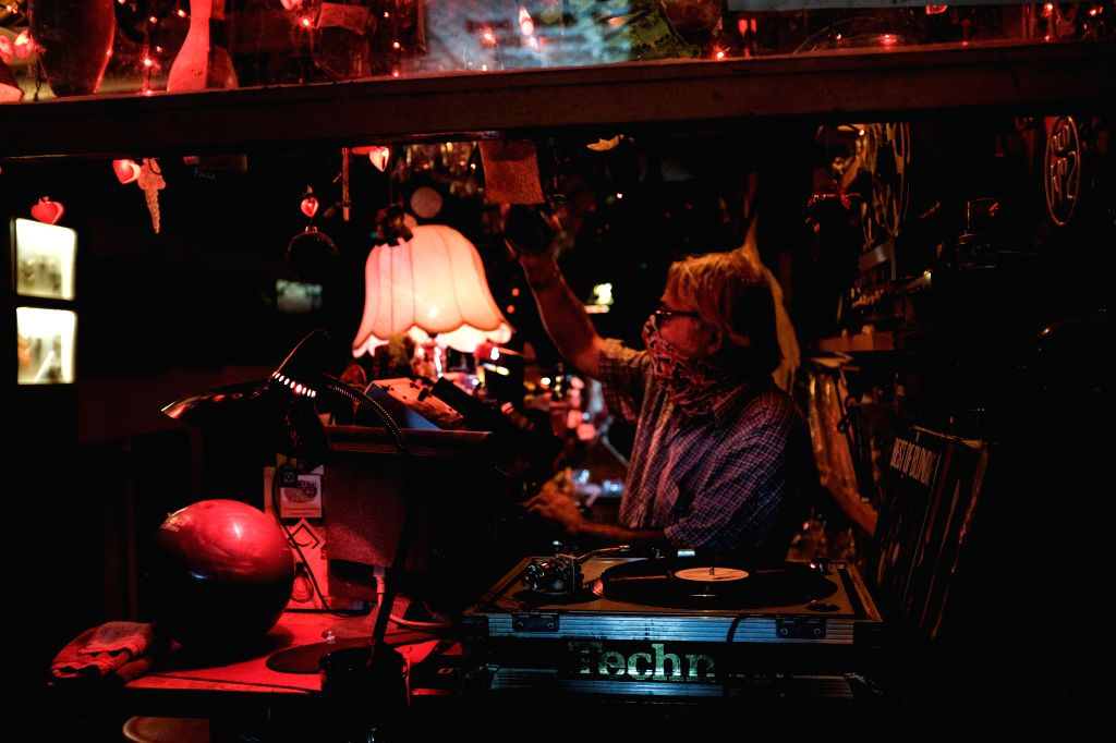 Ippokratis Navridis, owner of a small bar, plays music in his bar in downtown Athens, Greece, on Aug. 26, 2020. To contain the recent resurgence of the COVID-19 ...