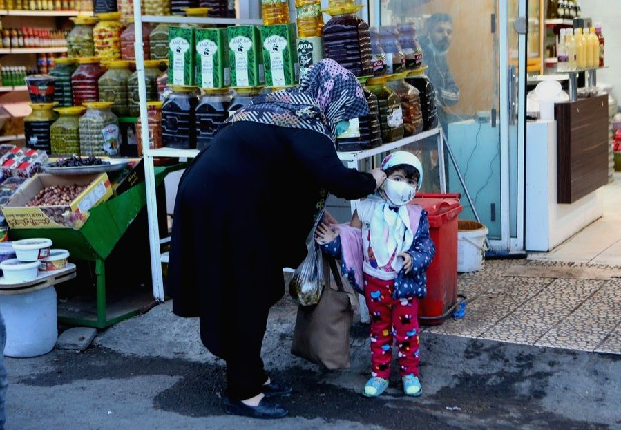 Iran, Nov. 16  A woman adjusts her child's face mask at a bazaar in Mashhad, Iran, Nov. 16, 2020.