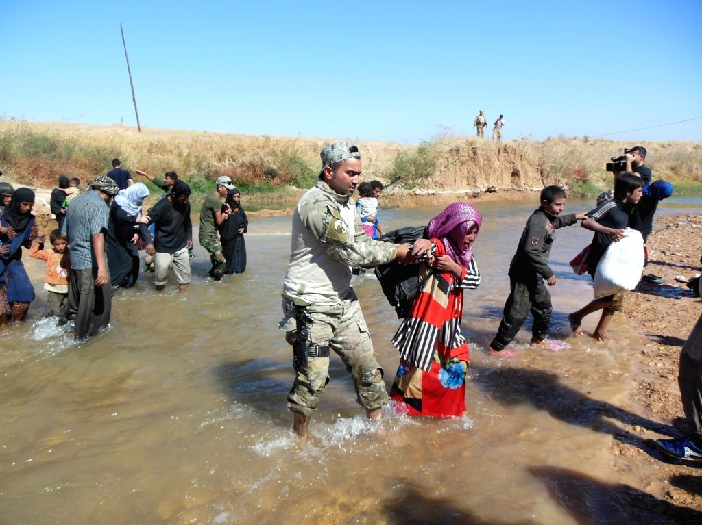 IRAQ, Oct. 5, 2017 - An Iraqi soldier helps a woman cross a river near the city of Kirkuk , Iraq, on Oct. 4, 2017. Because of the conflict between Iraqi forces and Islamic State militants in the ...