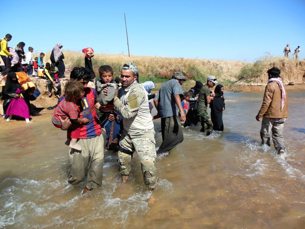 IRAQ, Oct. 5, 2017 - An Iraqi soldier helps civilians cross a river near the city of Kirkuk, Iraq, on Oct. 4, 2017. Because of the conflict between Iraqi forces and Islamic State militants in the ...