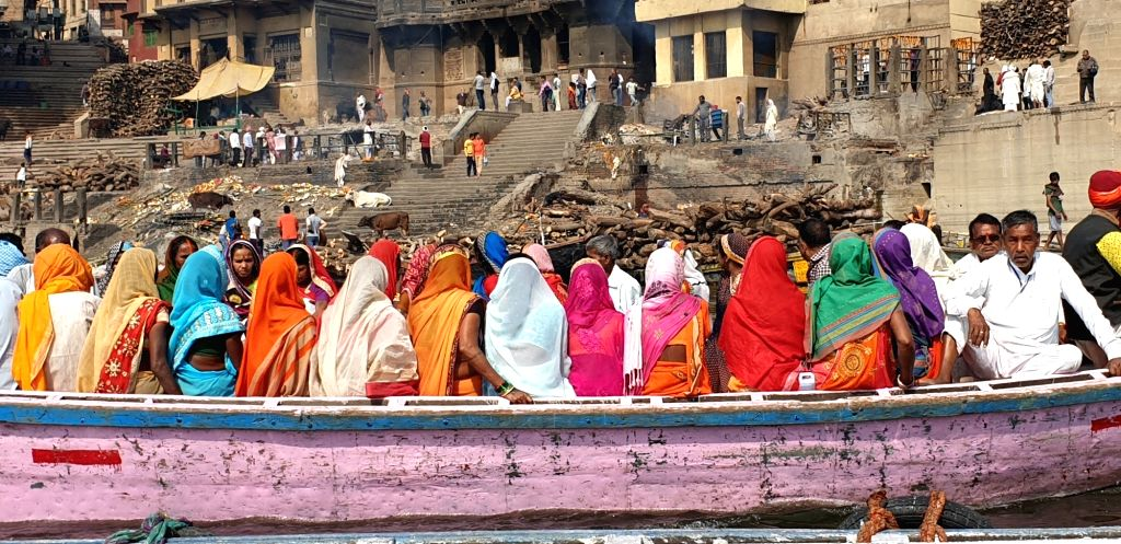 Irony of vibrant life facing the dark inevitable. Women clad in colourful sarees row past the wooden logs that are used for cremation, in Varanasi.