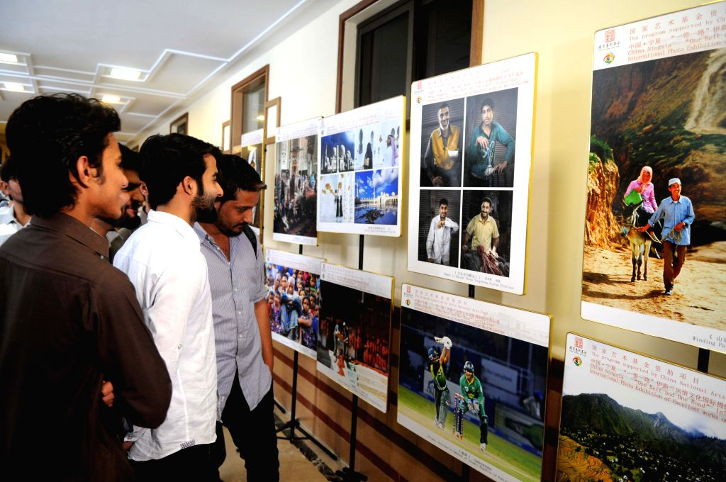 "ISLAMABAD, April 22, 2016 - Pakistani students look at photos during ""One Belt and One Road"" Initiatives International Photo Exhibition on Excellent Works of Muslim Customs at National ..."
