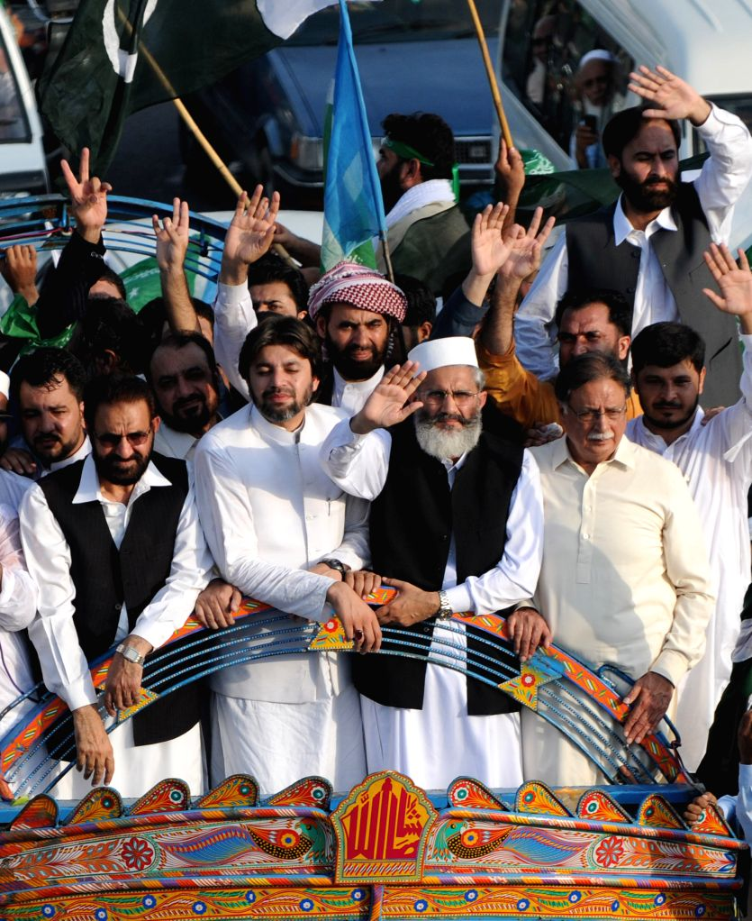 Chief of Jamaat-e-Islami Siraj-ul-Haq (C) waves to supporters during a protest rally against Israeli offensive on Gaza Strip in Islamabad, capital of Pakistan on .