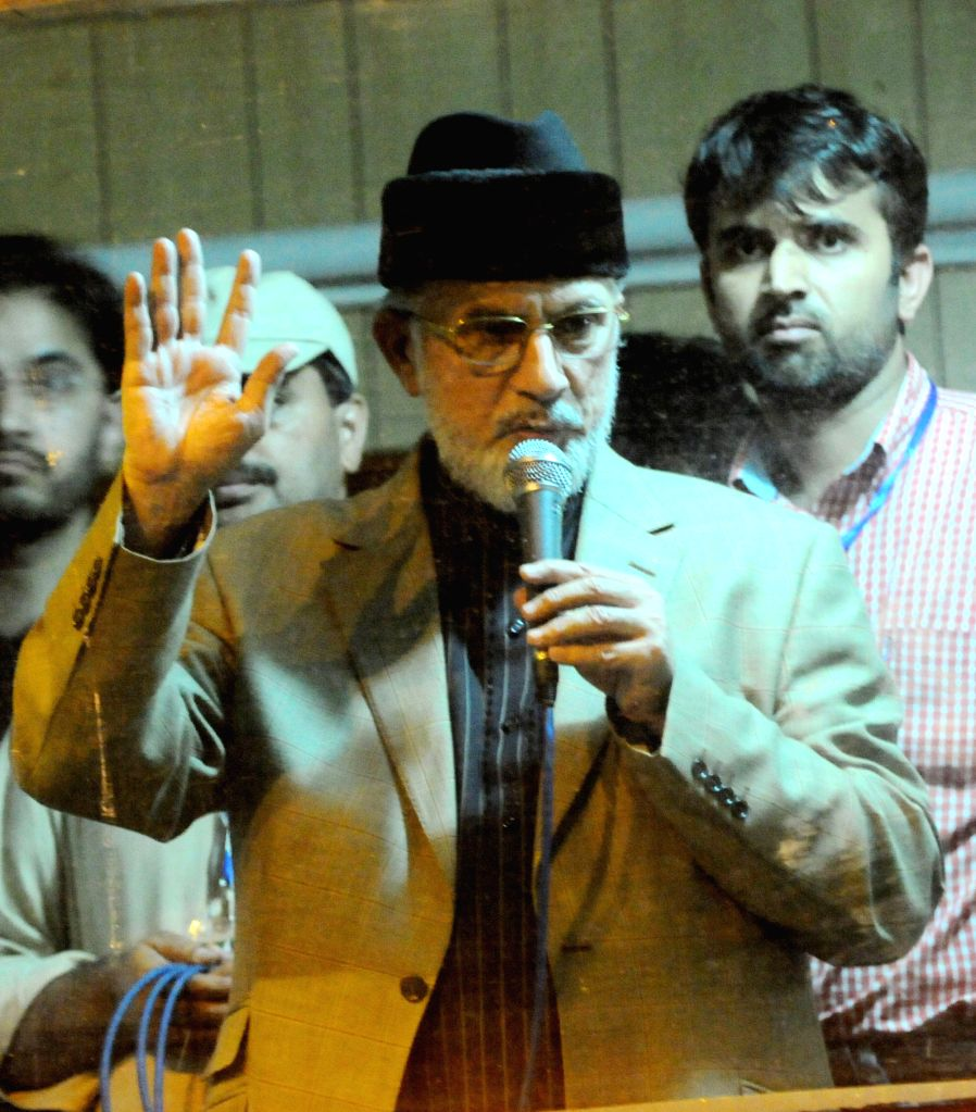 Religious anti-government leader Tahir-ul-Qadri (front) addresses supporters inside a shipping container in front of the parliament building during a protest in ..