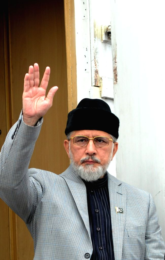 Pakistani anti-government leader Tahir-ul-Qadri waves to supporters as he arrives for congregational Friday prayers held at an anti-government protest site in ...