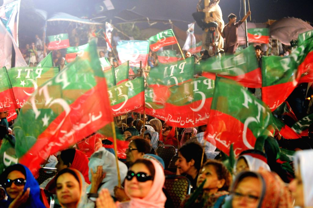 Supporters of Imran Khan, head of opposition political party Pakistan Tehrik-e-Insaf, wave flags in an anti-government protest for the 12th day in Islamabad, ... - Imran Khan