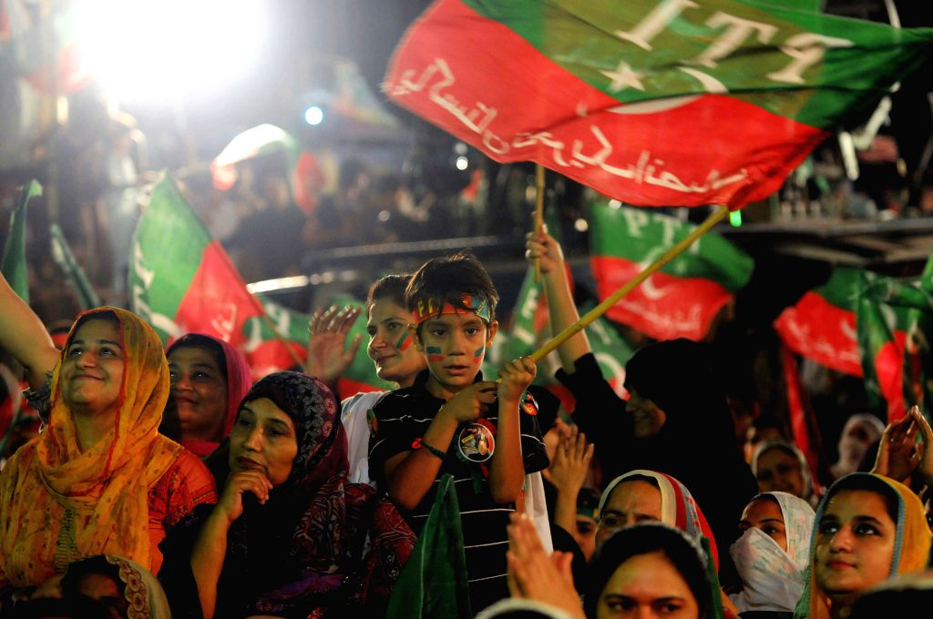 Supporters of Pakistan Tehrik-e-Insaf leader Imran Khan wave flags during an anti-government protest in front of the parliament building in Islamabad, capital of . - Nawaz Sharif and Imran Khan