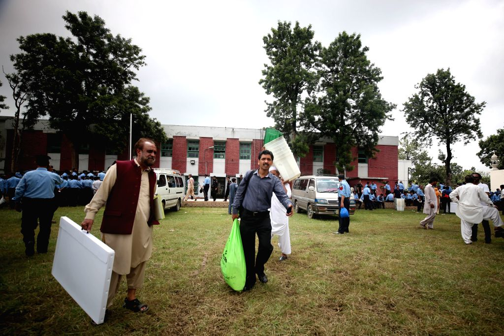 ISLAMABAD, July 24, 2018 - Election officials carry ballot boxes and voting materials at a distribution center in Islamabad, capital of Pakistan, on July 24, 2018. Pakistan will hold its general ...