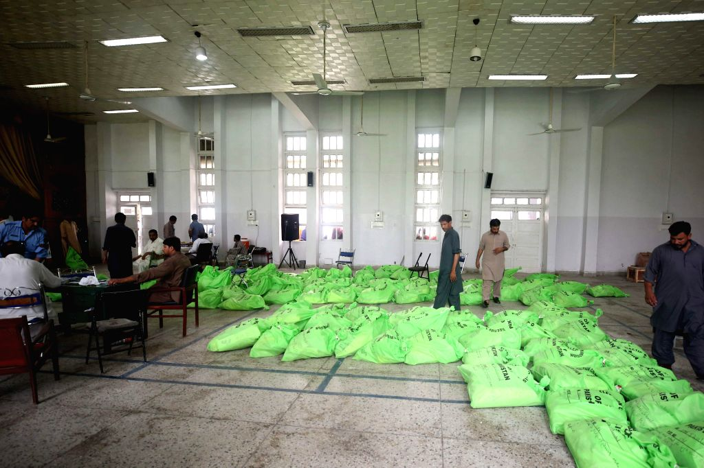 ISLAMABAD, July 24, 2018 - Election officials look at voting materials at a distribution center in Islamabad, capital of Pakistan, on July 24, 2018. Pakistan will hold its general elections on July ...