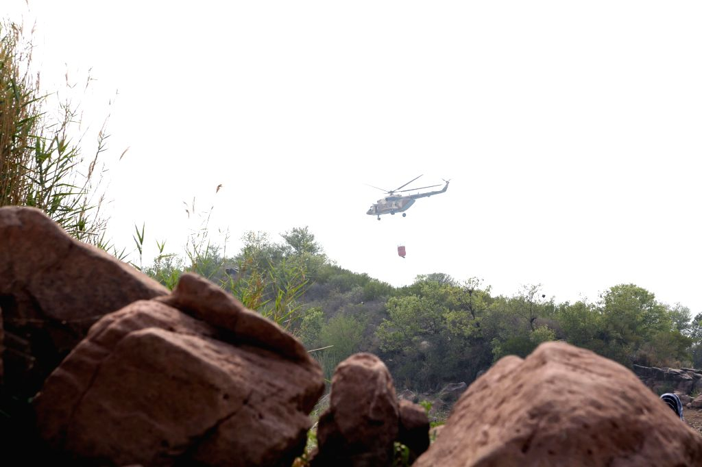 ISLAMABAD, June 1, 2018 - An army helicopter carries water on its way to extinguish a fire from the forest around the Margalla Hills in Islamabad, capital of Pakistan on June 1, 2018. Firefighters ...