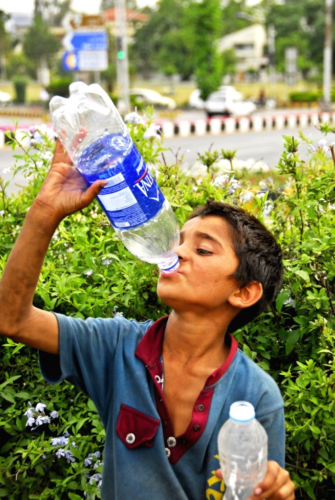 ISLAMABAD, May 27, 2017 - A boy drinks water on a street during heat wave in Islamabad, capital of Pakistan, on May 27, 2017. Temperature reached over 45 degrees Celsius in many parts of the country.