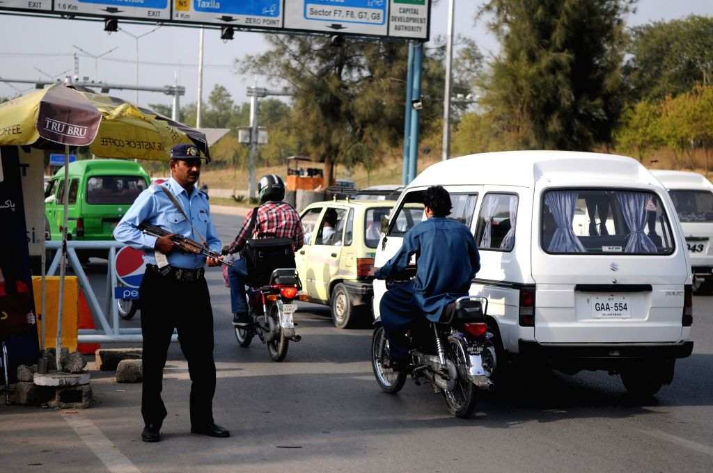 ISLAMABAD, Oct. 25, 2016 - A policeman stands guard at a checkpoint due to security high alert following an attack at a police training center in Quetta, in Islamabad, capital of Pakistan, Oct. 25, ...
