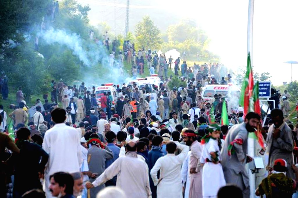 Pakistani protesters run from tear gas during clashes with riot police in Islamabad, capital of Pakistan on Sept. 1, 2014. At least 15 more people were injured on