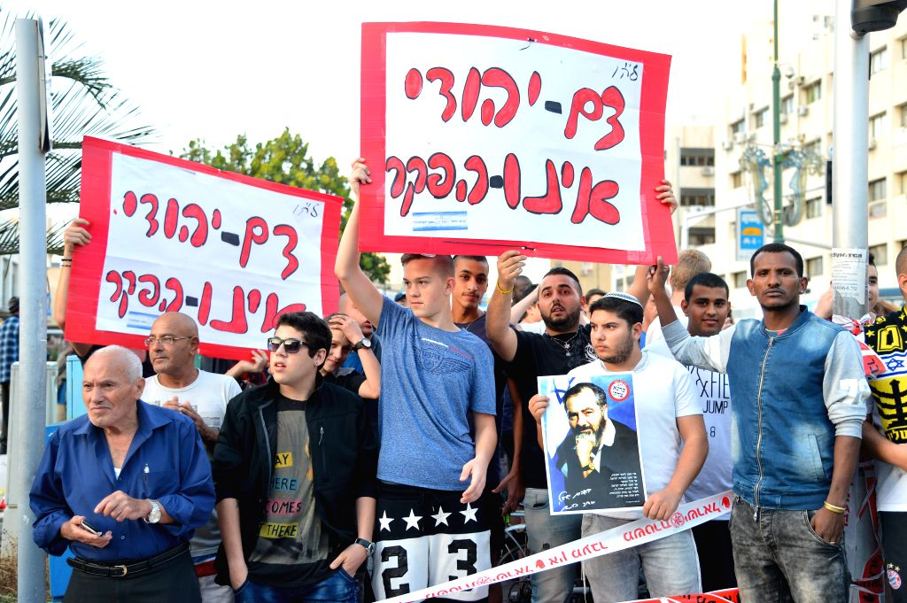 "Israeli protesters hold placards reading in Hebrew ""Jewish blood is not forfeit"" on the scene of a stabbing in Rishon Letzion, a major city south of Tel ..."