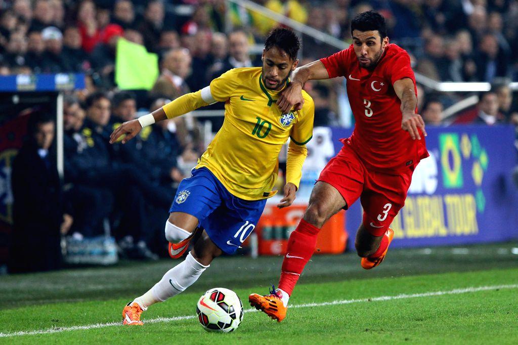 Brazil's Neymar (L) vies with Turkey's Ismail during a friendly match in Istanbul, Turkey, Nov. 12, 2014. Brazil won 4-0.