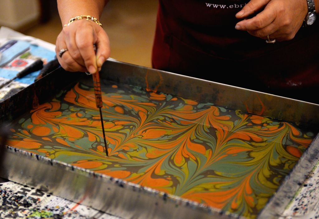 One Ebru artist outlines the drawing with a tool in Istanbul, Turkey, on Dec. 22. Ebru is a traditional Islamic and Turkish painting art, and can be defined as ...