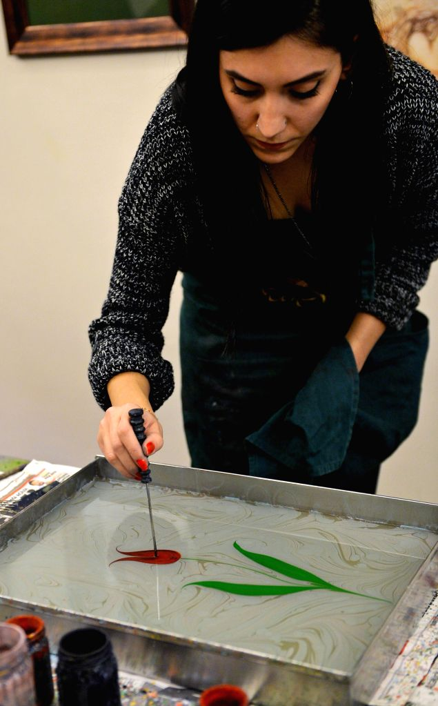 One Ebru artist paints a tulip in the water in Istanbul, Turkey, on Dec. 22. Ebru is a traditional Islamic and Turkish painting art, and can be defined as painting