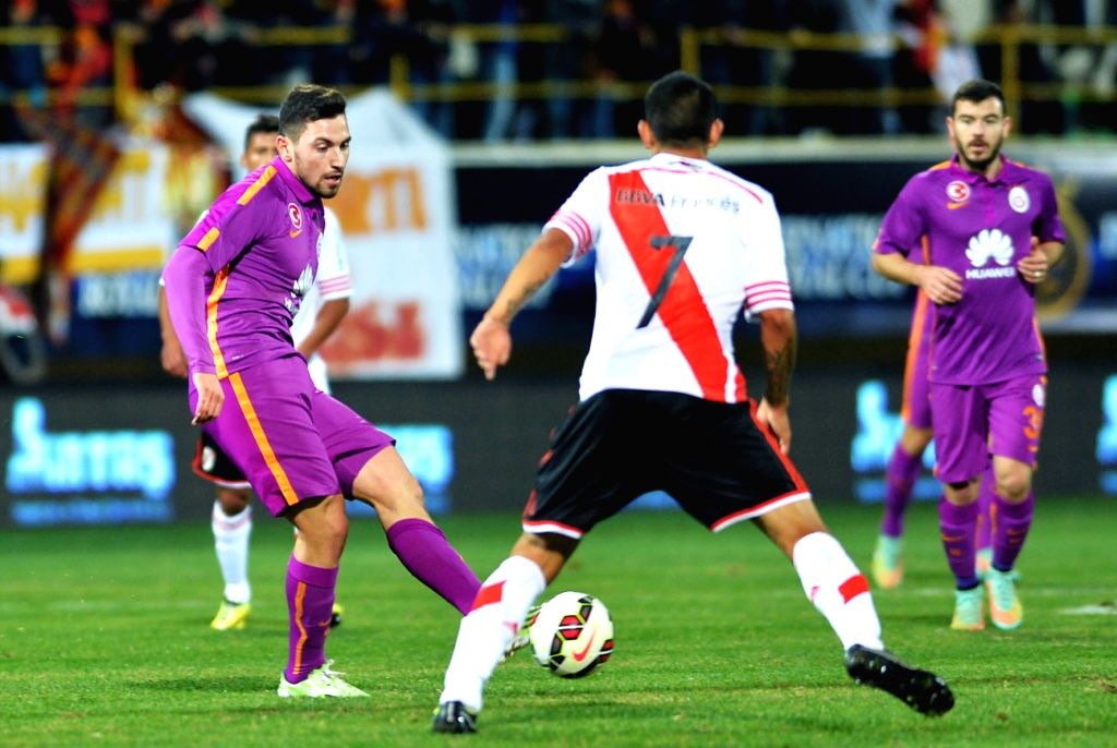 Sinan Gumus (L) of Galatasary passes the ball during the International Royal Cup match against River Plate of Argentina at Alanya Oba Stadium in Antalya, Turkey, ..