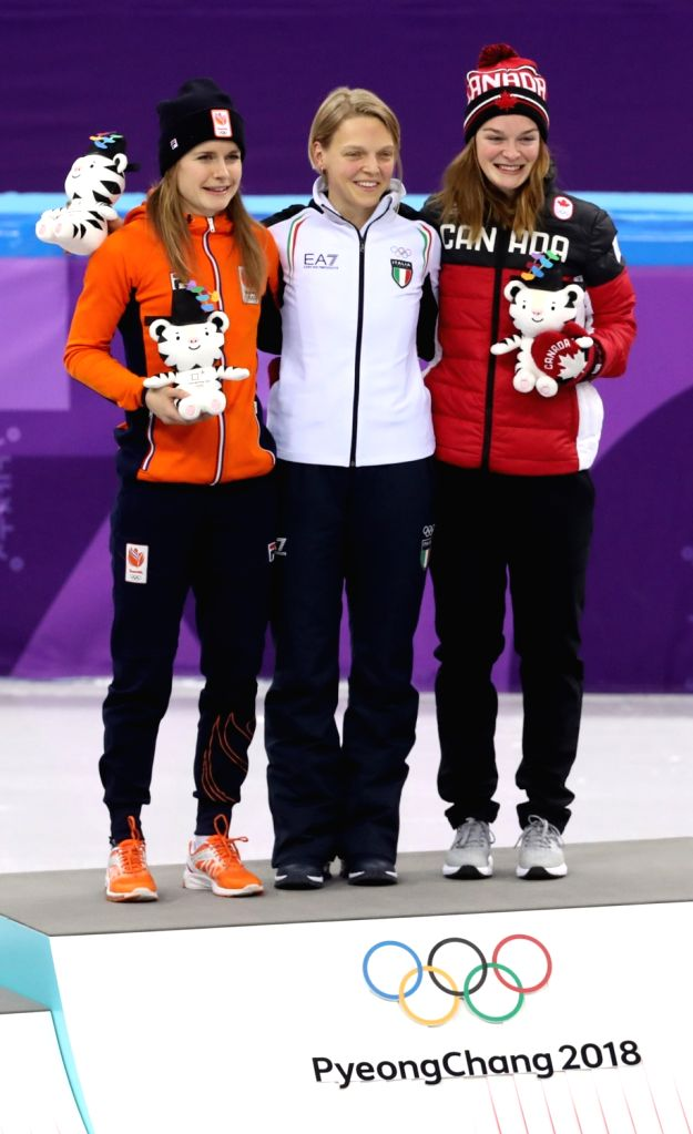 Italian short track skater Arianna Fontana (C) poses together with the top two runners-up on the podium after winning the gold medal in the women's 500-meter final at Gangneung Ice Arena ...