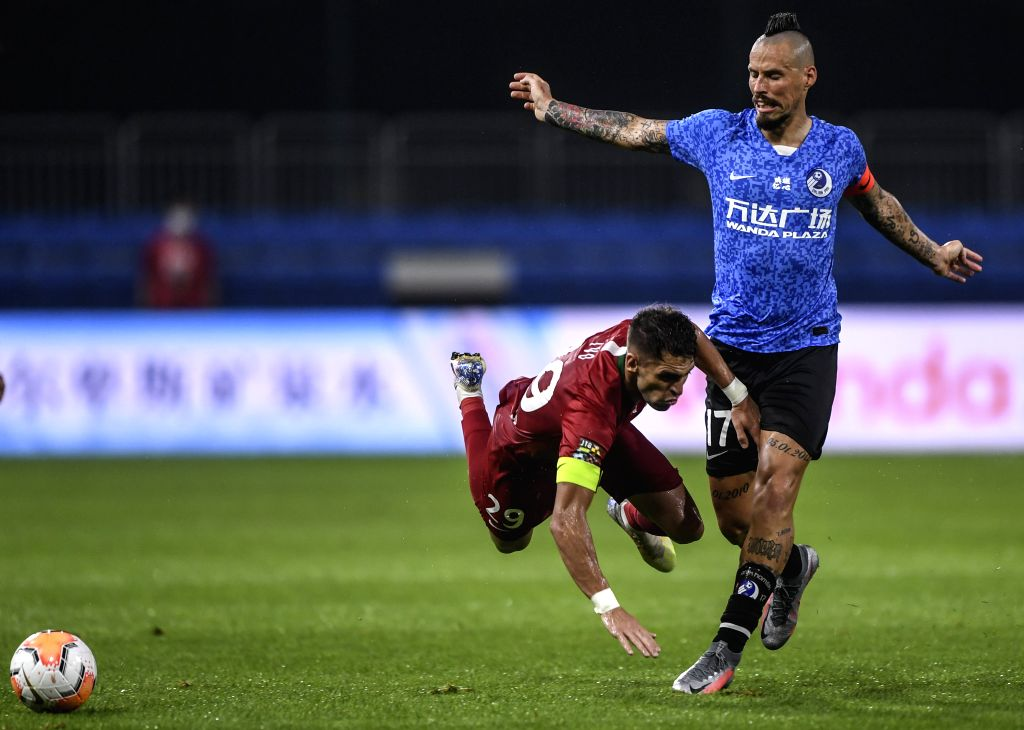 Ivo (L) of Henan Jianye FC vies with Marek Hamsik of Dalian Yifang FC during the second round match between Dalian Yifang FC and Henan Jianye FC at the postponed ...