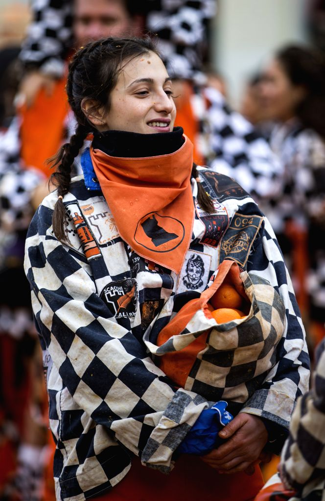"""IVREA, Feb. 13, 2018 - A member of a team holds a bag of oranges during an annual historical carnival """"Battle of the Oranges"""" in the northern Italian town of Ivrea, Italy, on Feb. 12, 2018."""