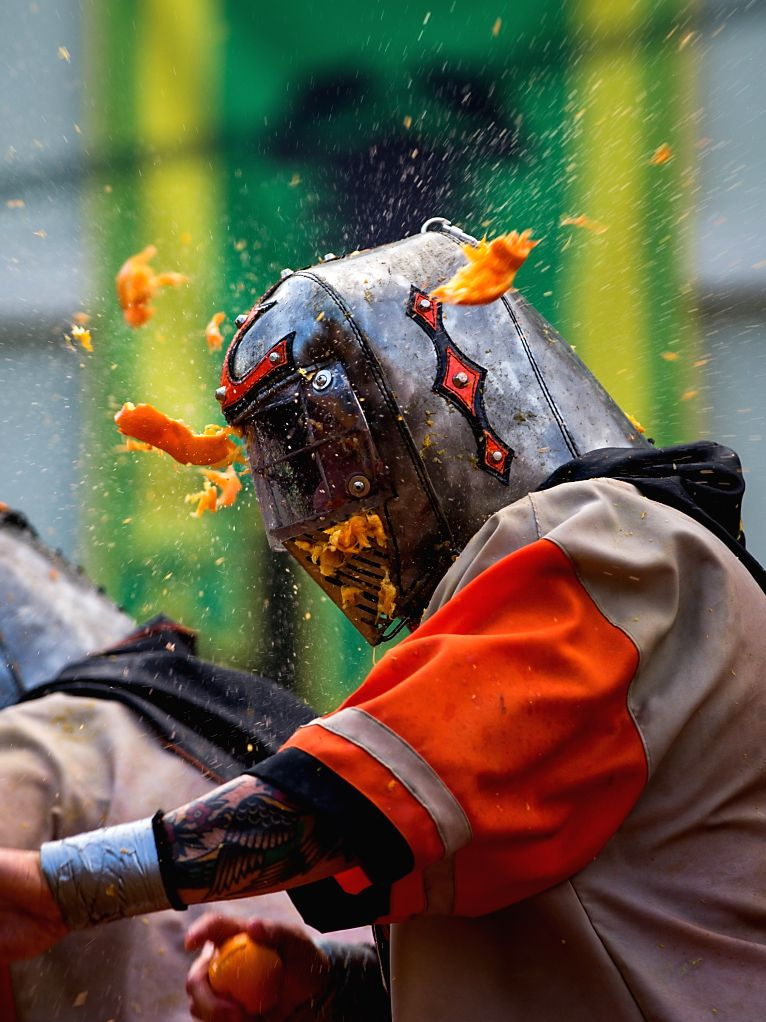 """IVREA, Feb. 13, 2018 - A member of a team is hit by oranges during an annual historical carnival """"Battle of the Oranges"""" in the northern Italian town of Ivrea, Italy, on Feb. 12, 2018."""