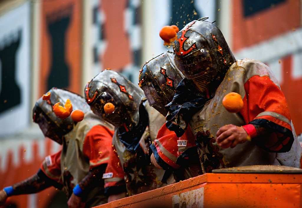 "IVREA, Feb. 13, 2018 - Members of a team fight with oranges during an annual historical carnival ""Battle of the Oranges"" in the northern Italian town of Ivrea, Italy, on Feb. 12, 2018."