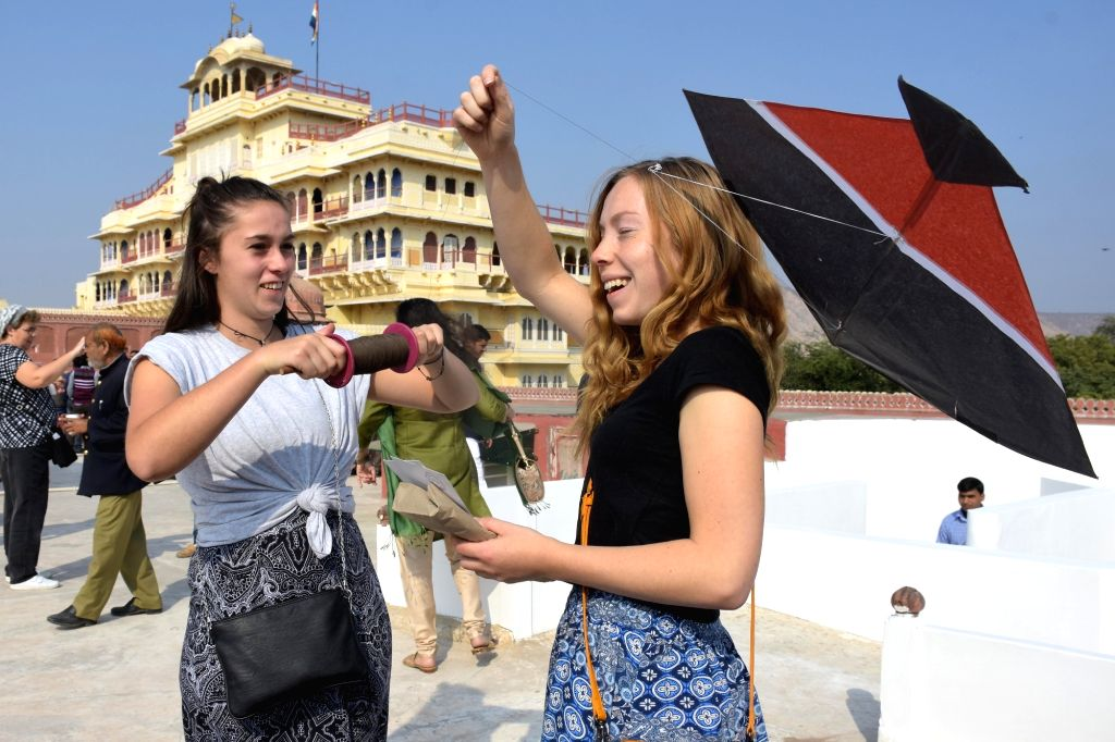 Jaipur: Foreign tourists try their hands on kite flying during the Kite festival at City Palace in Jaipur, on Jan 13, 2016. (Photo: Ravi Shankar Vyas/IANS)