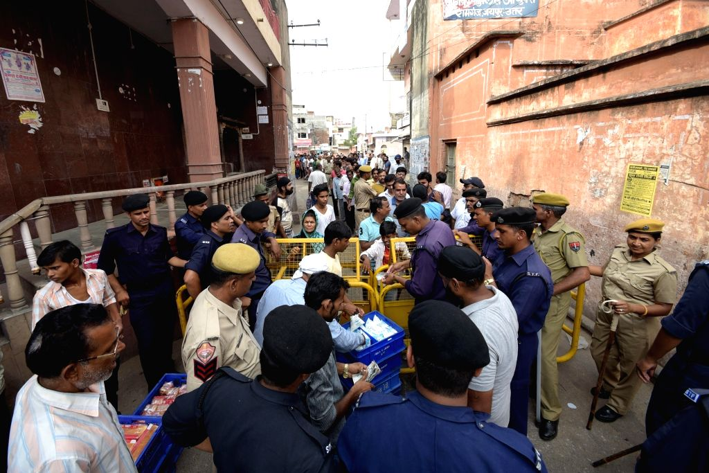 Jaipur: Police personnel distribute essential items among locals as curfew was imposed following violence that erupted between locals and the police on the night of Sept 8 after a policeman hit a person sitting on a motor bike with a baton in Jaipur