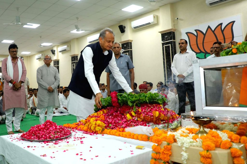 Jaipur: Rajasthan Chief Minister Ashok Gehlot pays tributes to state BJP chief Madan Lal Saini at the party state headquarters, in Jaipur on June 25, 2019. Saini, who was admitted at the All India Institute of Medical Sciences in New Delhi last week  - Ashok Gehlot