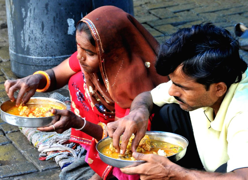 Jaipur, Rajasthan, India, Thursday, 1 Aug, 2013, A Couple enjoying food at the roadside food stall, in Jaipur. Roadside stalls are very popular and common in the streets of India for the locals as the prices are only a mere fraction of the ones avail - Raghuveer Singh