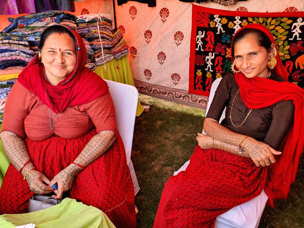 Jaipur: Women sitting with their ears adorned with big pretty earrings pierced into quite a big-sized ear hole (of around 2-3 inch) and their complete arms and hands heavily tattooed with little green dots have become the centre of attraction at the