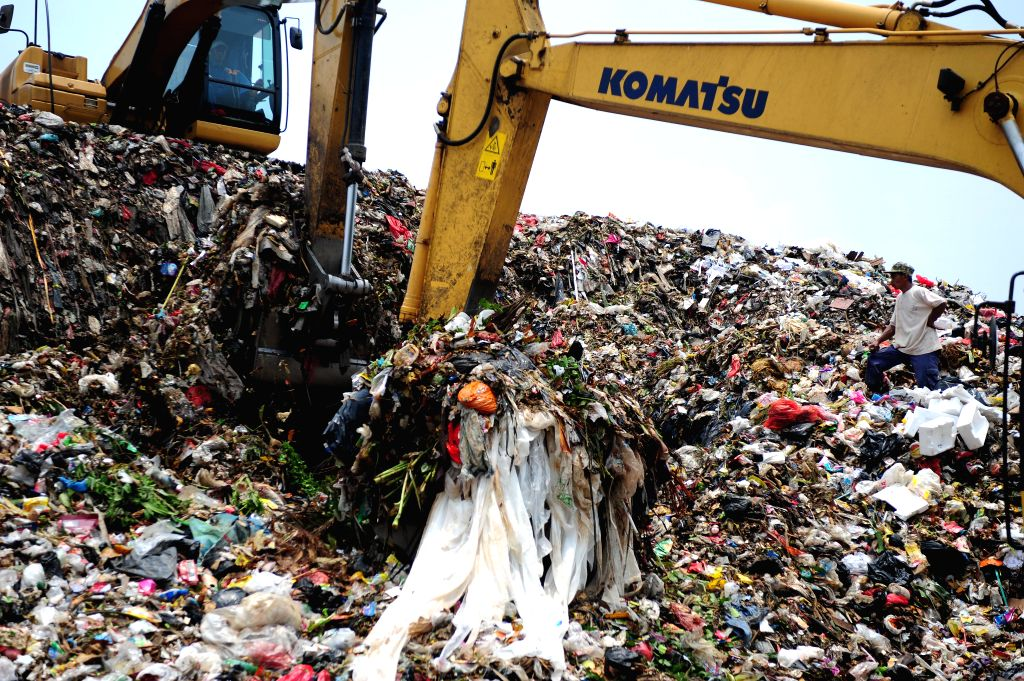 Jakarta: A scavenger sorts out plastics at a garbage dump in Depok, West Java Province, Indonesia, Oct. 16, 2014. Indonesian Environment Minister Balthasar Kambuaya on Oct. 8 signed and launched the nation's new plans to address the Stockholm Convent - Balthasar Kambuaya