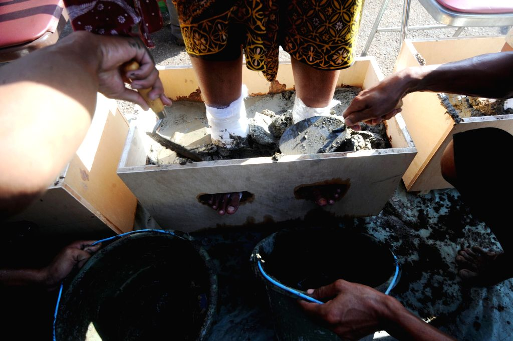 JAKARTA, April 12, 2016 - People use cement to bury a woman's feet to refuse the construction of a cement factory built in their village, in Jakarta, Indonesia, April 12, 2016. The protestors want to ...