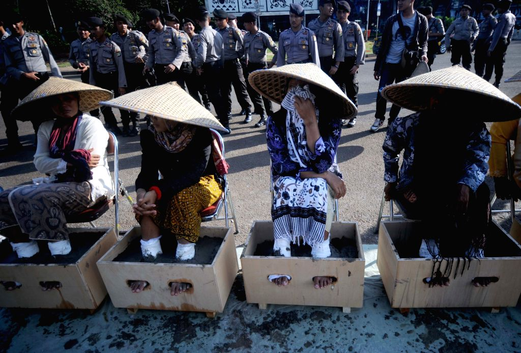 JAKARTA, April 12, 2016 - Women from Kendeng, Central Java take part in a rally in front of the Presidential Palace by cementing their feet to refuse the construction of a cement factory built in ...
