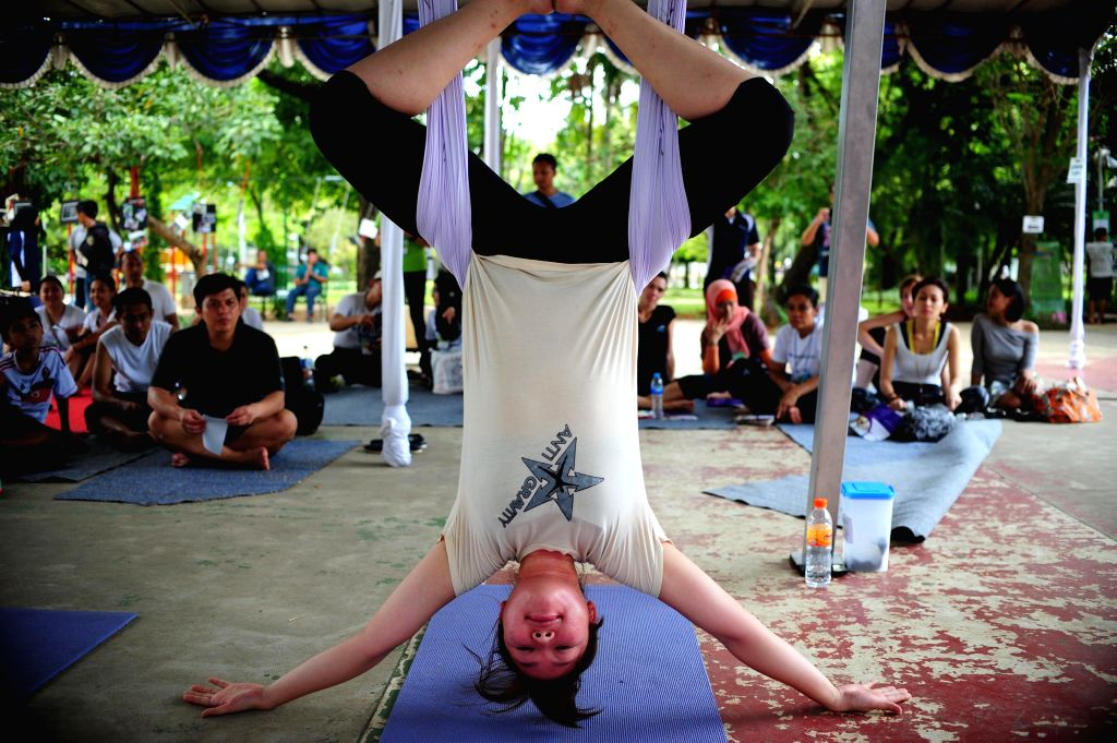 A Yoga instructor exemplifies the movement during the Yoga Gembira Festival 2014 in Jakarta, Indonesia, April 18, 2014. The event is held from April 18 to 20, ...