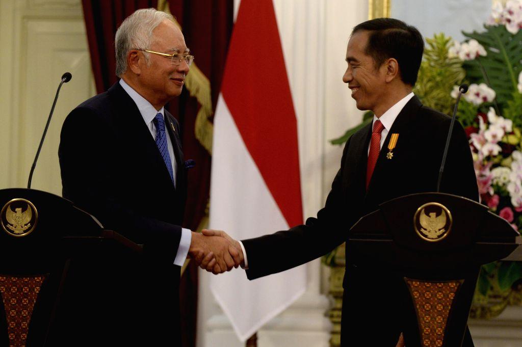 JAKARTA, Aug. 1, 2016 - Indonesian President Joko Widodo (R) shakes hands with Malaysian Prime Minister Najib Razak at a press conference after the 11th Annual Consultation between Malaysia and ... - Najib Razak