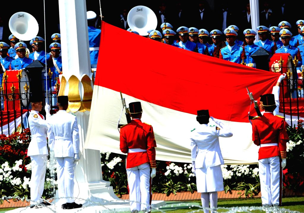 Indonesian flag-raising squads give salute to a national flag during a celebration of the country's 68th independence anniversary at the Presidential Palace in