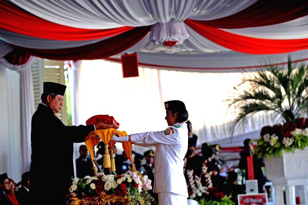 Indonesian President Susilo Bambang Yudhoyono (L) gives the national flag to a member of  flag-raising squads during a celebration of the country's 68th ...