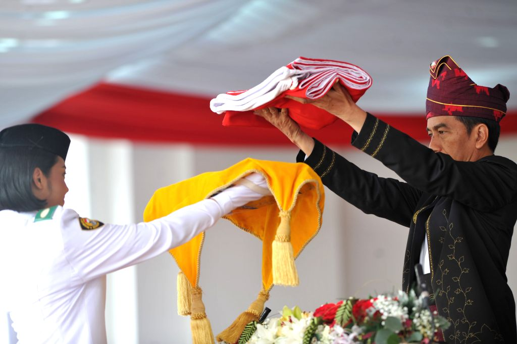 JAKARTA, Aug. 17, 2017 - Indonesian President Joko Widodo (R) presents the national flag to a student during the ceremony to mark the 72nd Independence Day of Indonesia at Merdeka Palace in Jakarta, ...