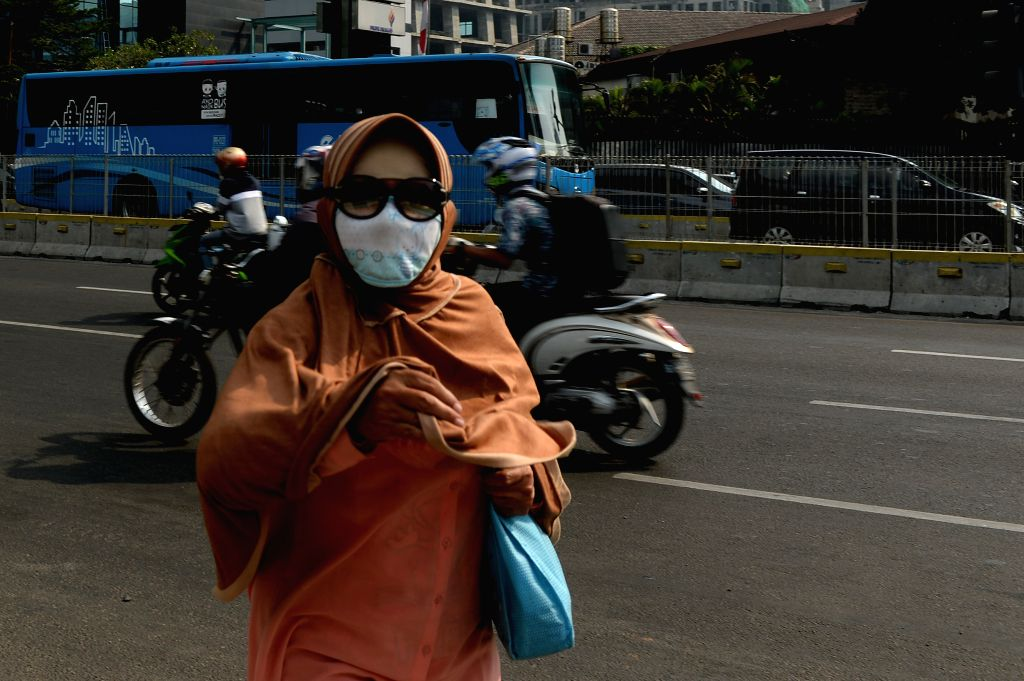 JAKARTA, Aug. 2, 2019 - A woman wears a mask due to air pollution on street in Jakarta, capital of Indonesia, Aug. 2, 2019.