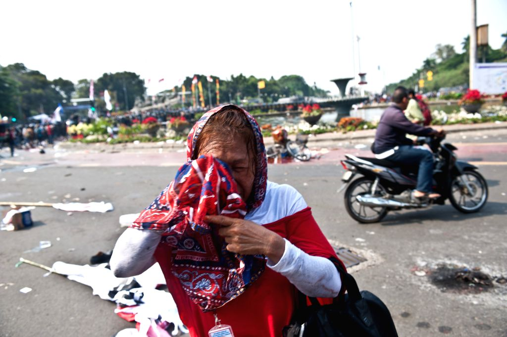 A supporter of losing presidential candidate Prabowo Subianto clears eyes after riot police fired tear gas during a rally near the constitutional court in Jakarta, .