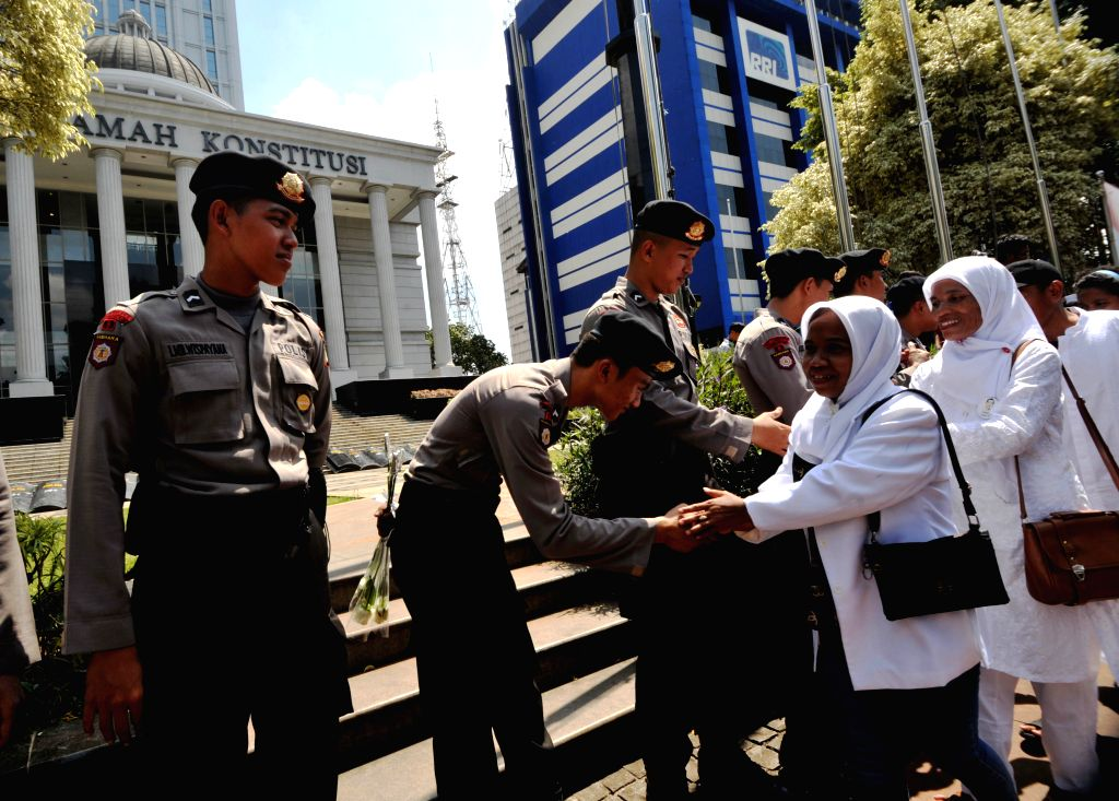 People greet to Indonesian police officers while they are deployed to secure the Constitutional Court in Jakarta, Indonesia, Aug. 5, 2014. About 22,000 Indonesian ...